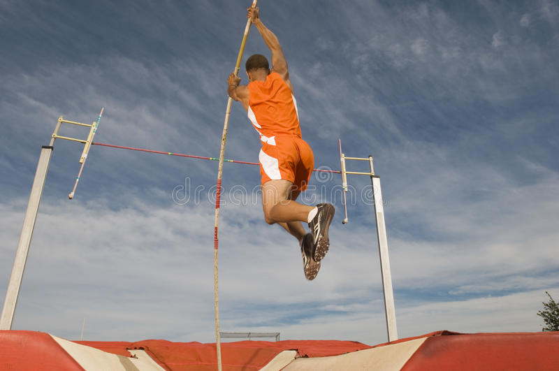 Male Athlete Pole Vaulting. Against cloudy sky stock photo