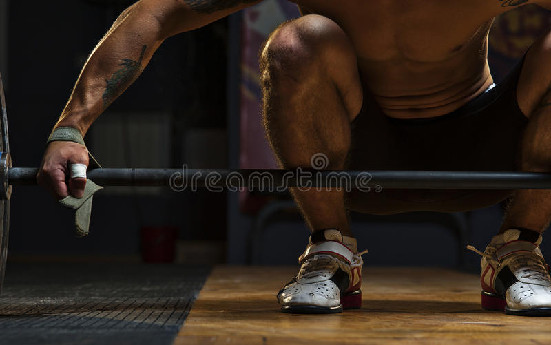 Male athlete preparing for exercise with barbell. Cropped shot of male athlete preparing for dead lift exercise with barbell. Weightlifting, power lifting royalty free stock image