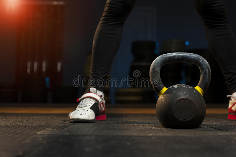 Male athlete preparing for kettlebell workout. In gym. Weightlifting training. Sports, fitness concept stock image