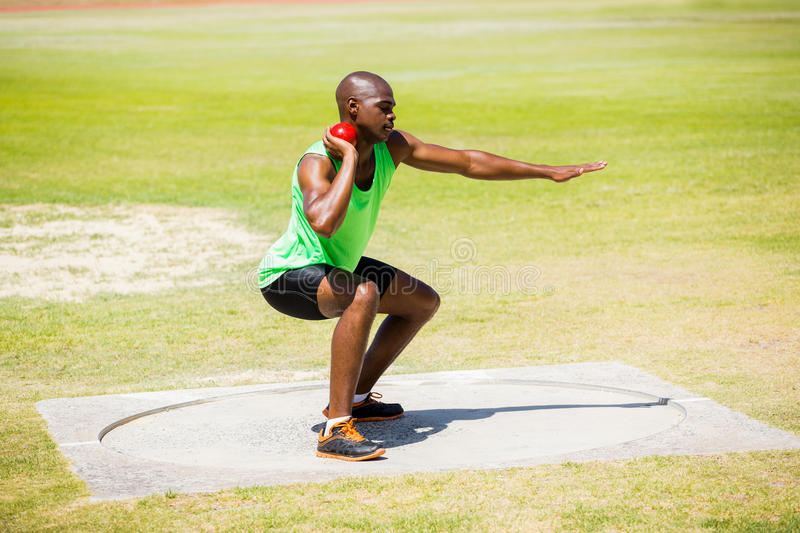 Male athlete preparing to throw shot put ball. In stadium stock photo