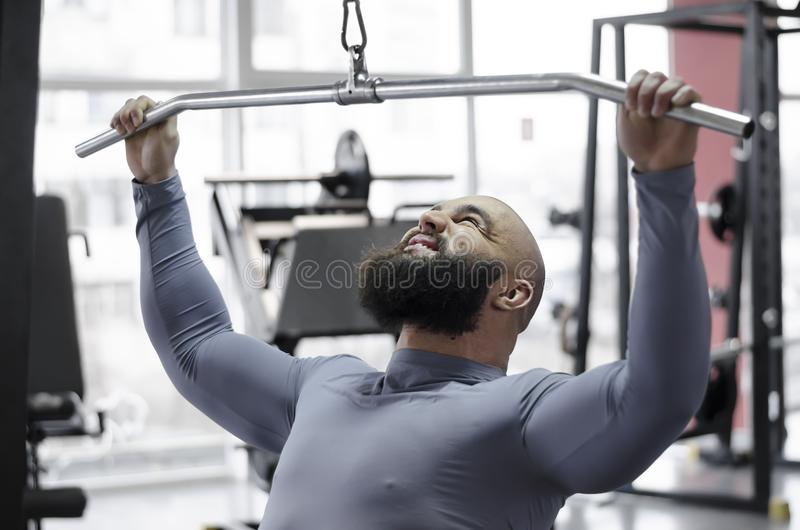 Male athlete pulling down heavy weight with strained face, sports training. Stock footage royalty free stock photos