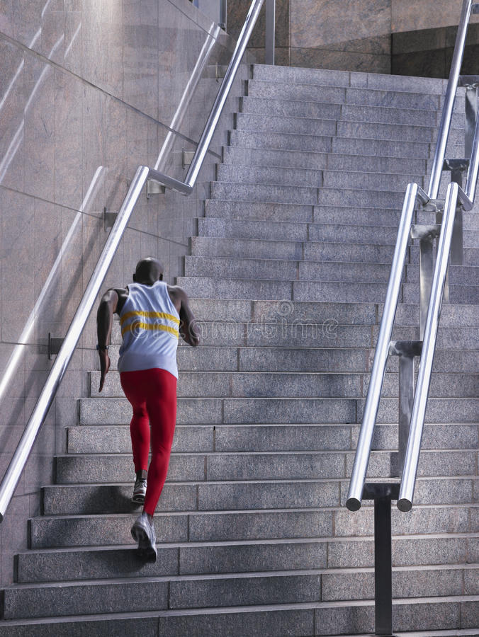 Male Athlete Running Up Staircase Outdoors. Rear view of a male athlete running up staircase outside building royalty free stock image