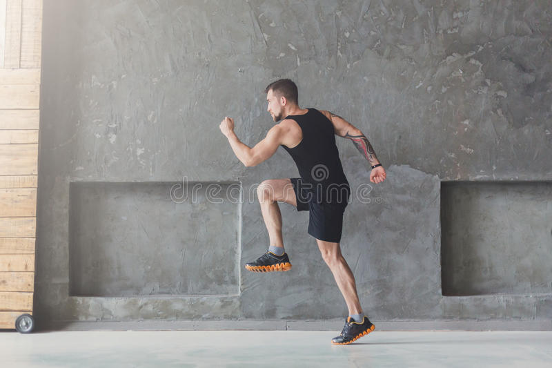 Male athlete sprinter running, exercising indoors. Workout. Male athlete sprinter running, exercising indoors, jogging in training room, side view, full length stock photography