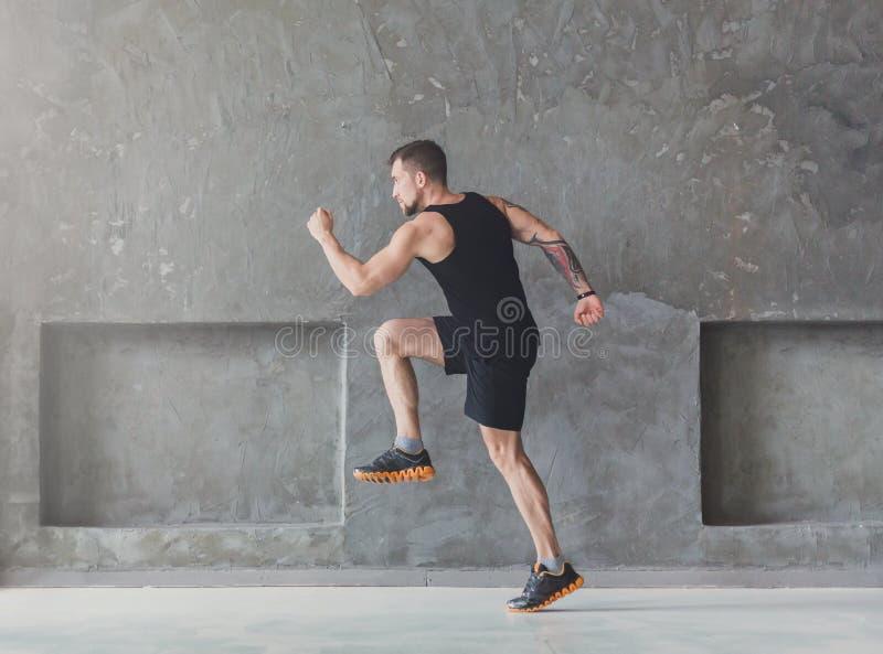 Male athlete sprinter running, exercising indoors stock image