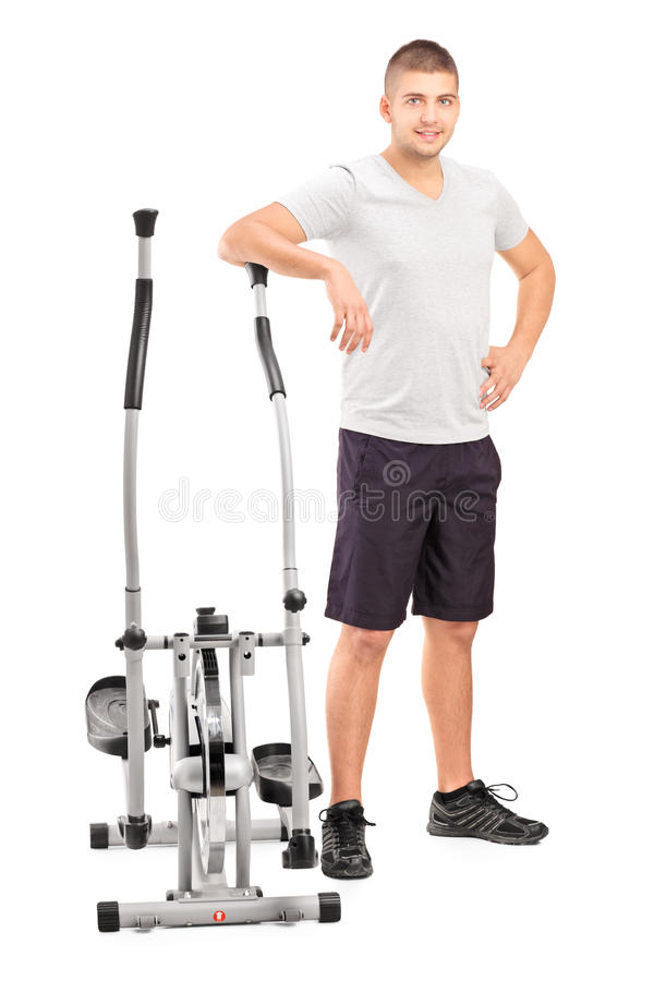 Male athlete standing next to a cross trainer machine