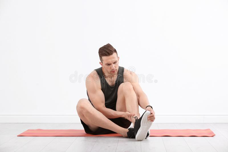 Male athlete suffering from leg pain indoors stock photography