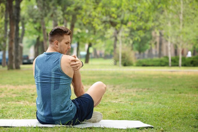 Male athlete suffering from shoulder pain. During training outdoors royalty free stock photo