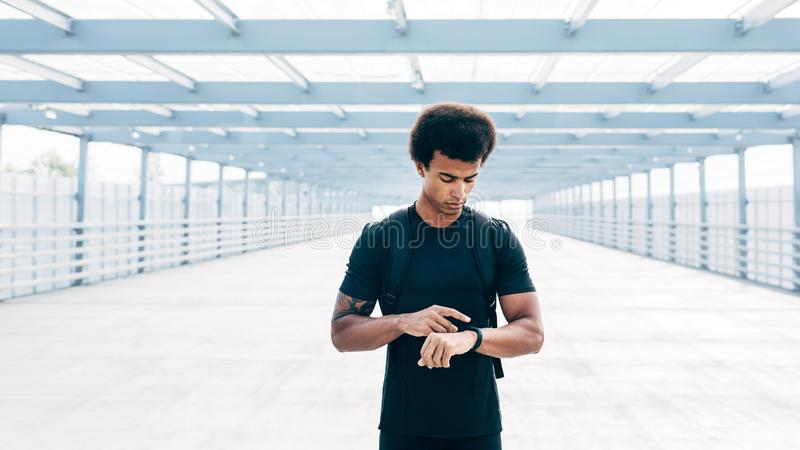Male athlete wearing sport clothes. Checking activity tracker stock photos