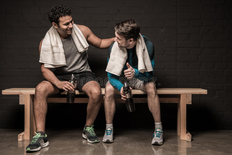 Male athletes resting and conversing at gym locker room. Handsome male athletes resting and conversing at gym locker room stock photo