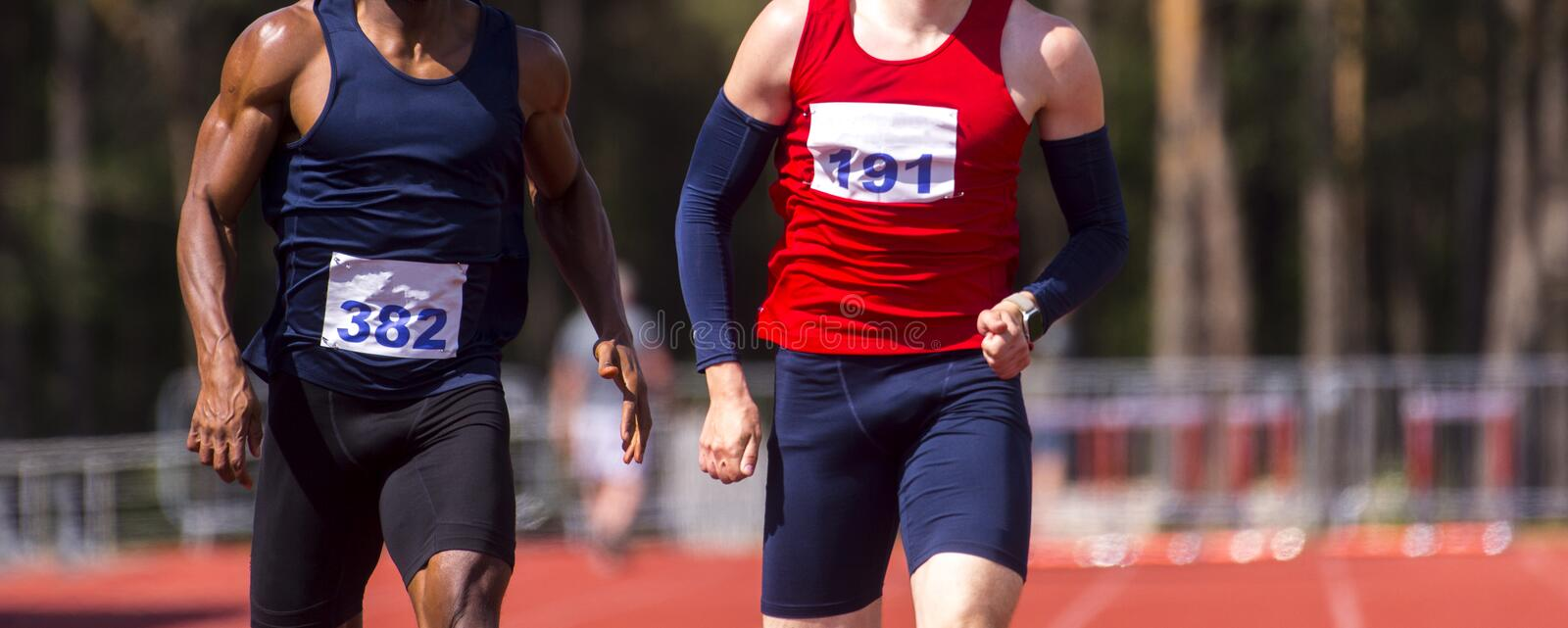 Male athletes sprinting. Two men in sport clothes run at the running track in professional stadium stock photography