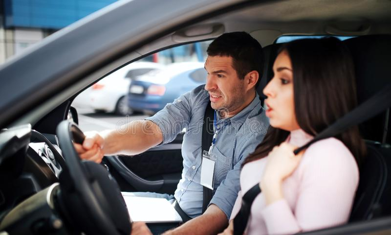 Male auto instructor takes exam in young woman. Avoiding car crash. Scared young woman hold hands on steering wheel royalty free stock photography