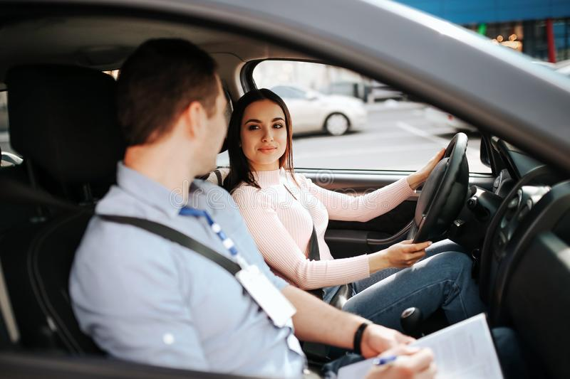 Male auto instructor takes exam in young woman. Calm peaceful confident female student look at teacher and smile. Hold stock photography