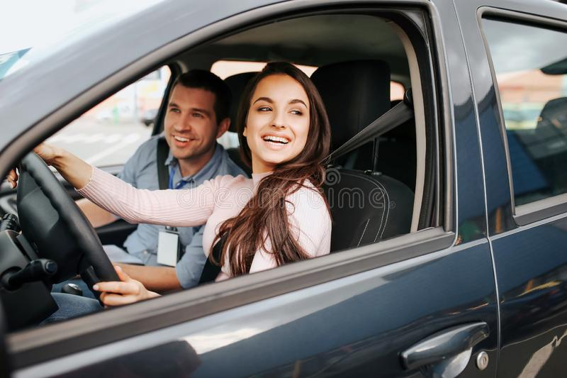 Male auto instructor takes exam in young woman. Cheerful attractive female driver posing at driver`s place. Look from. Car. Hold hands on sheering wheel royalty free stock photos