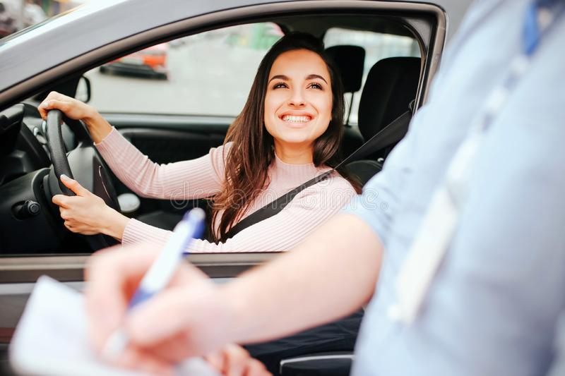 Male auto instructor takes exam in young woman. Cheerful attractive model look at guy and smile. Holding hands on stock image