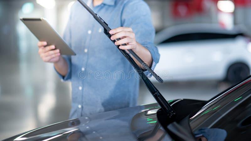 Male auto mechanic checking windshield wiper. Male auto mechanic holding digital tablet checking windshield wiper in auto service garage. Mechanical maintenance stock images