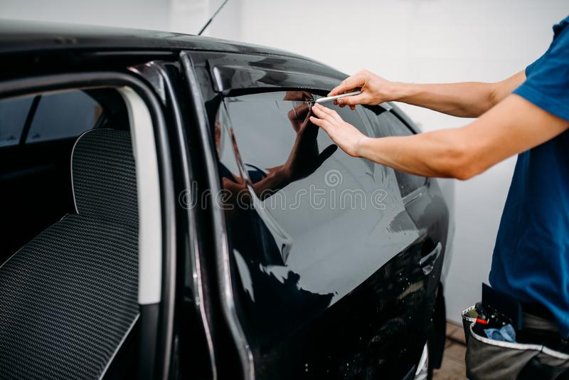 Male auto wrapper with blade, car tinting film stock image