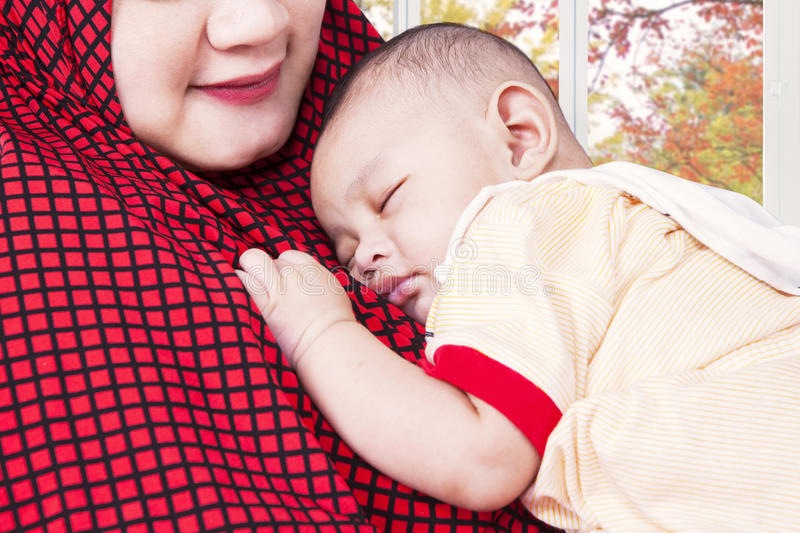 Male baby and his muslim mother. Lovely baby boy sleeping on mother's chest at home, shot with autumn background on the window stock photo