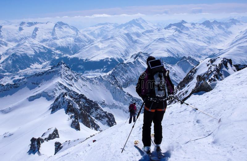 Male backcountry skier skiing down from a high alpine summit with a large backpack and solar panel stock photography