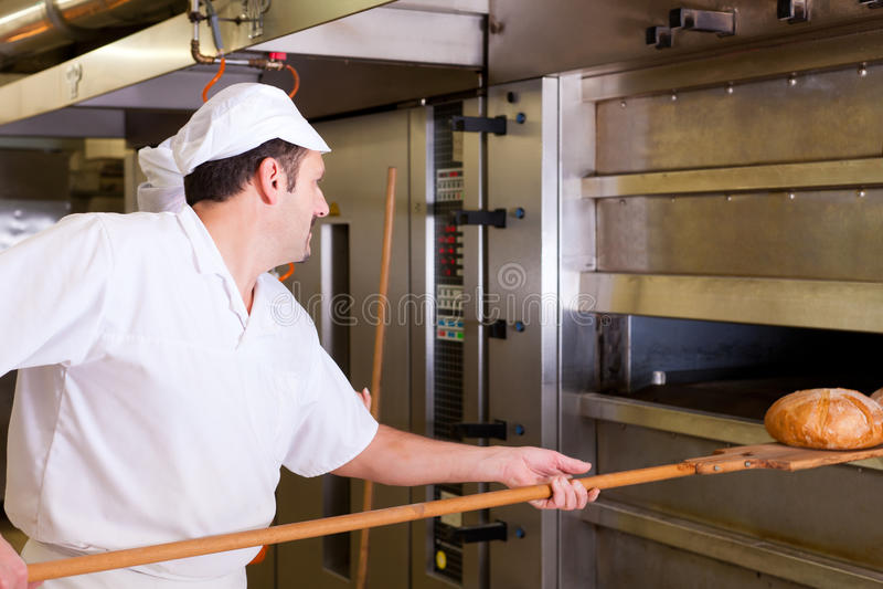 Male baker baking bread stock photography