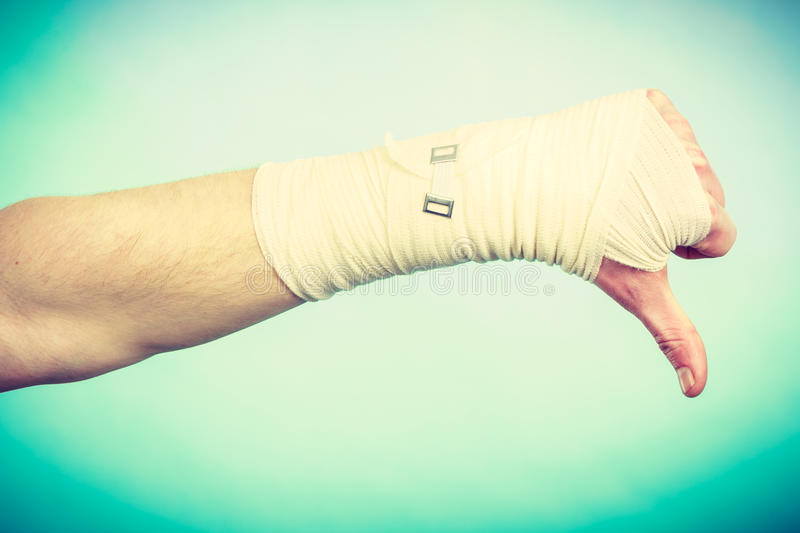 Male bandaged hand with thumb down sign. royalty free stock images