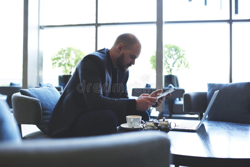 Male banker is using touch pad and net-book for preparing to conference. Young successful businessman is searching in web page needed information via digital stock photography