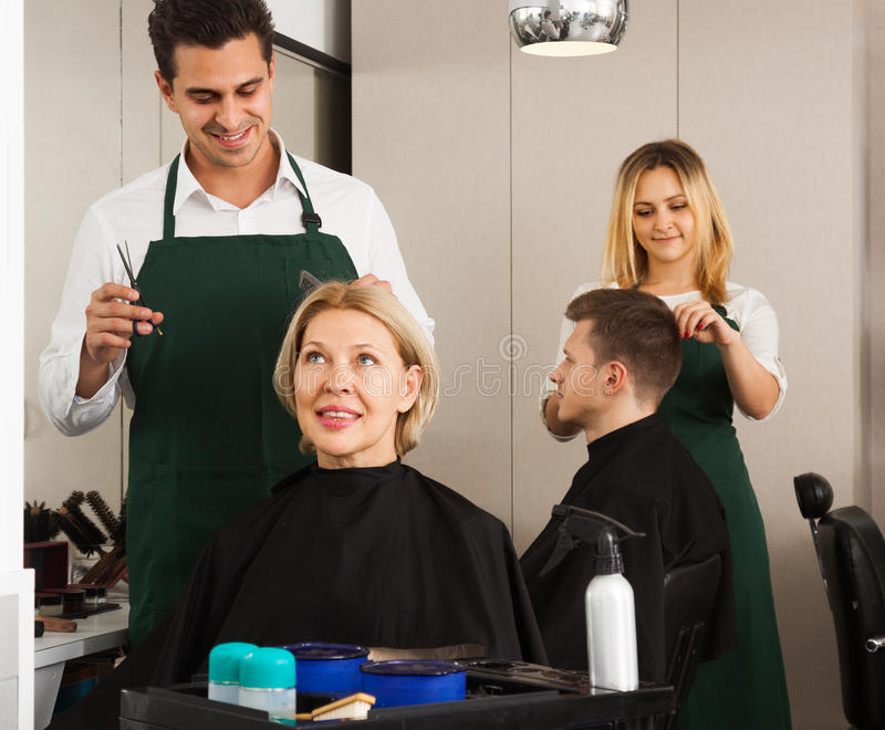 male barber cuts the mature woman. Woman hairdresser cuts a young guy stock photography