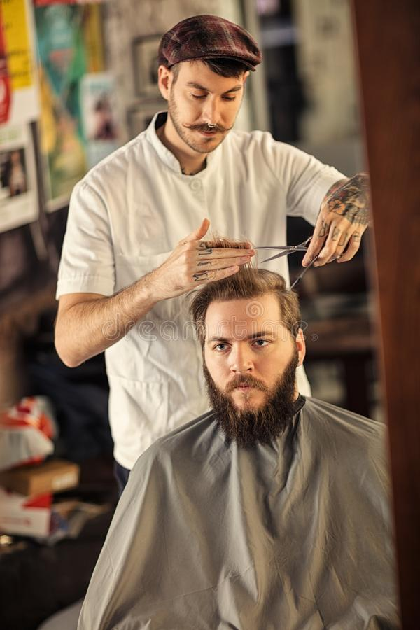 Male barber giving client haircut stock photography