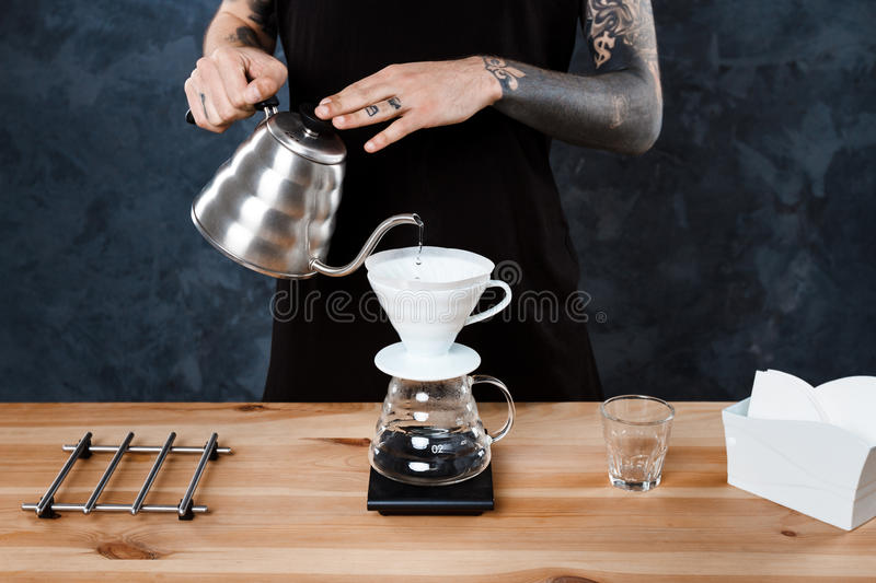 Male barista brewing coffee. Alternative method pour over. stock image
