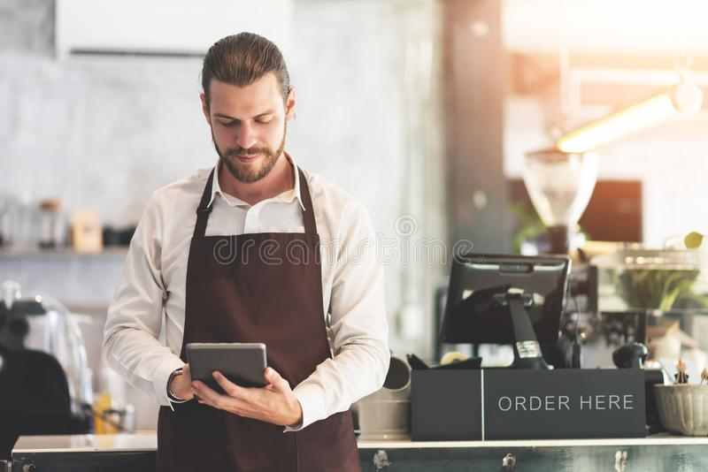 Male barista holding and looking at digital tablet royalty free stock photos