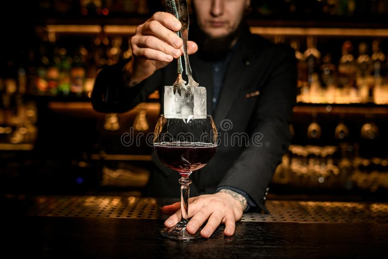 Bartender putting big ice cube in a cocktail. Male bartender with beard in suit putting big ice cube in an alcohol cocktail with special tongs royalty free stock photos