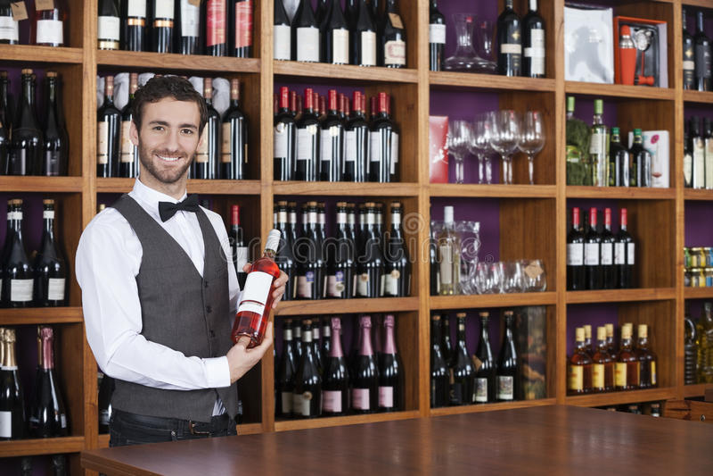 Male Bartender Holding Red Wine Bottle In Shop. Portrait of confident male bartender holding red wine bottle in shop stock images