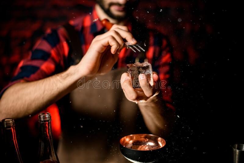 Male bartender holds large piece of ice and breaks it over glass. Male bartender holds large piece of ice and breaks it by special device over black glass royalty free stock photo