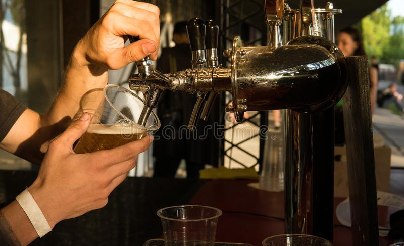 The male bartender pouring beer into a glass close-up. Street food royalty free stock image