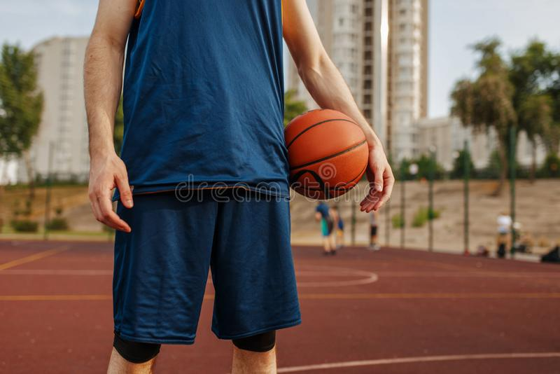 Male basketball player holds a ball, outdoor court. Male basketball player holds a ball on outdoor court. Male athlete in sportswear on streetball training royalty free stock photos