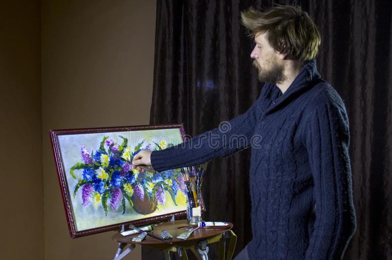 Male bearded artist in a dark sweater draws an artistic brush painting flowers still life in studio stock image