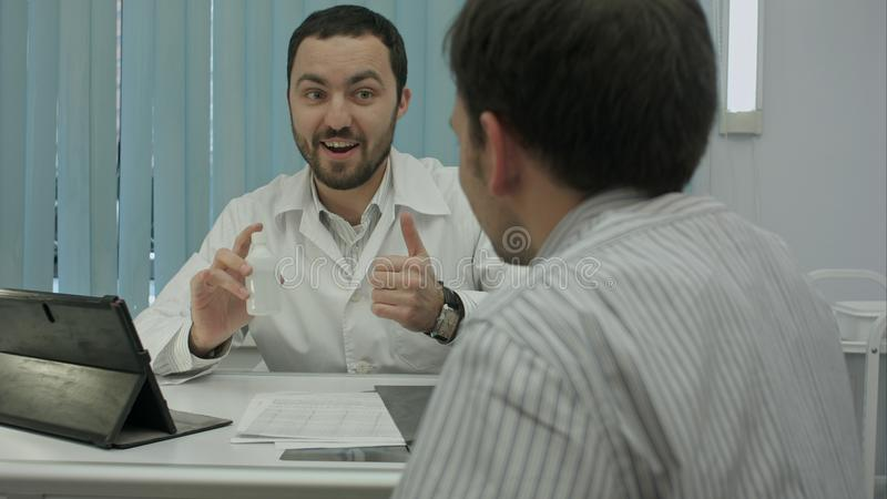 Male bearded doctor in clinic advertises preparation to client. royalty free stock photography