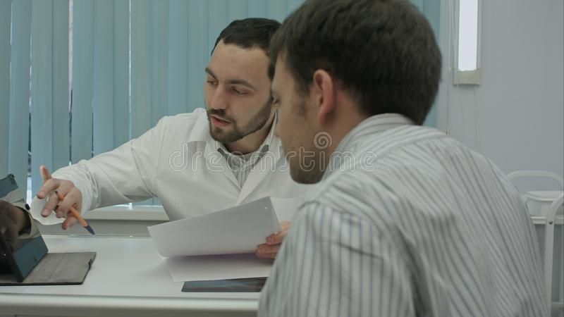 Male bearded doctor with tablet consult client. stock photo
