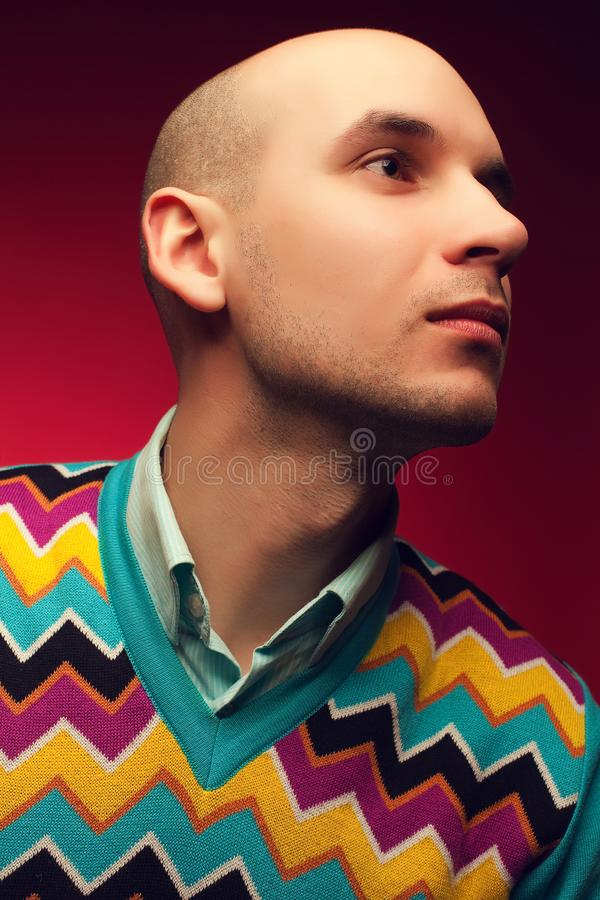 Male beauty concept. Profile portrait of a smiling elegant young & handsome bald man in stylish sweater posing over purple royalty free stock photography