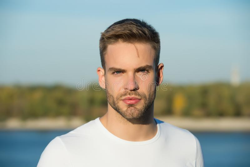 Male beauty standards. Handsome man stylish hairstyle. Handsome caucasian man looking at camera nature background. Ideal royalty free stock images