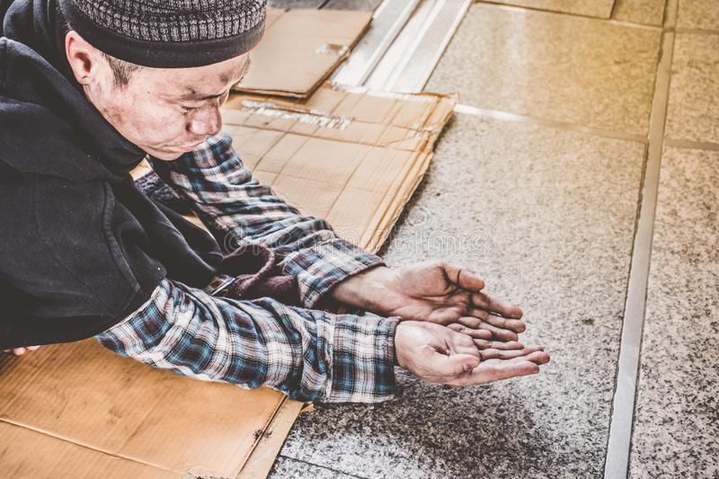 Male Beggar hands seeking money, coins from Human kindness. Homeless in the city royalty free stock photos