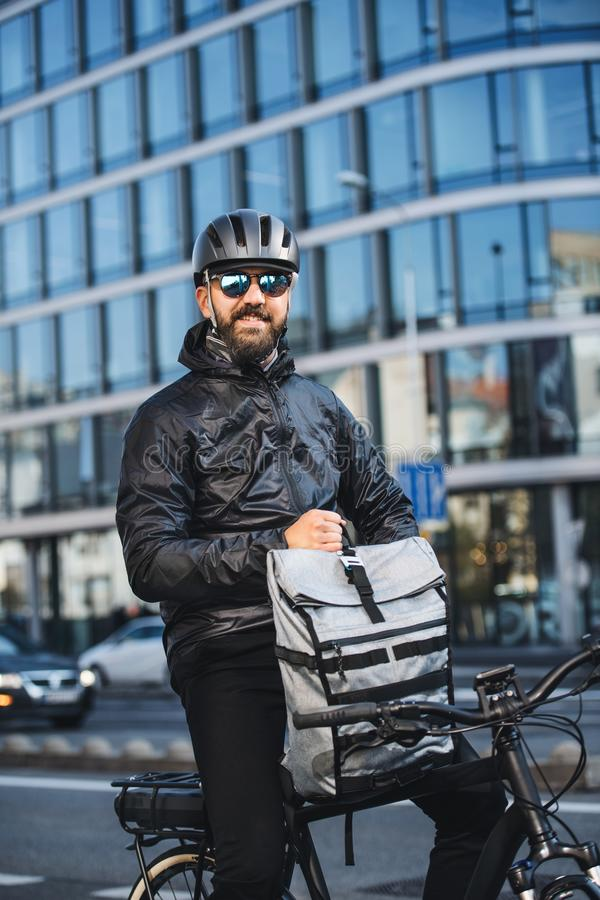 Male bicycle courier with backpack and sunglasses delivering packages in city. A portrait of male bicycle courier with backpack delivering packages in city royalty free stock images