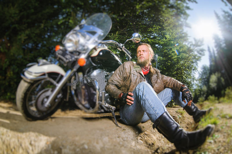 Male biker sitting on dirt road near motorcycle. Bearded biker posing with his shiny stylish custom made cruiser motorbike. Biker is sitting on the ground near royalty free stock photography