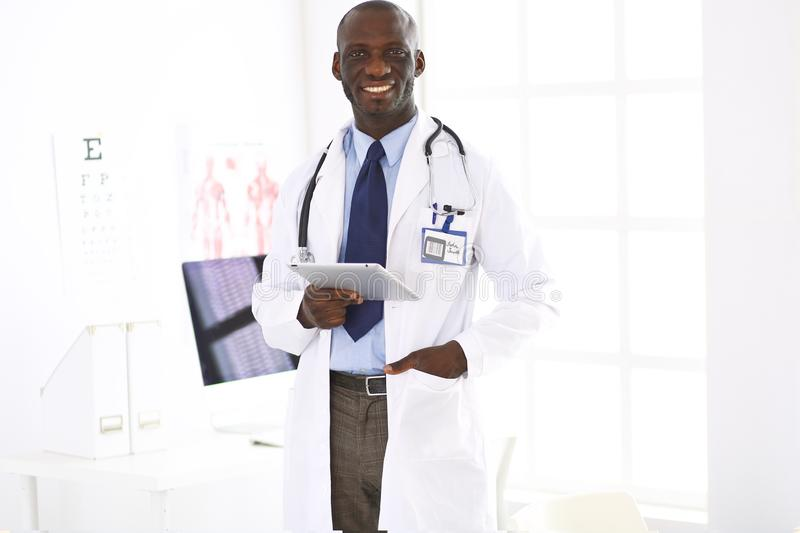 Male black doctor worker with tablet computer standing in hospital.  stock photo