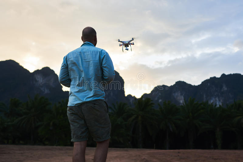 Male blog author is taking photos on flying multicopter during trip in Asia. Back view of man wanderer is shooting video with radio controlled drone, against royalty free stock photo