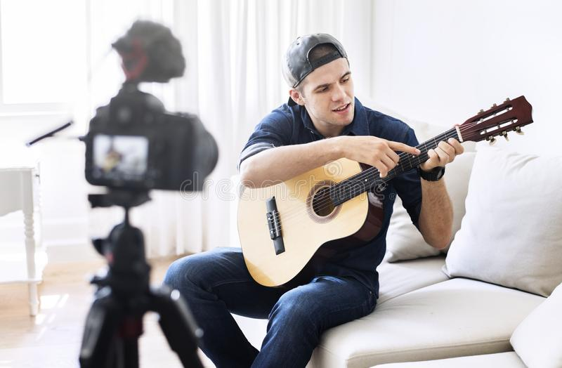 Male blogger recording music related broadcast at home stock image