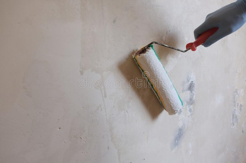 A male blue-gloved worker`s hand applies a primer to a wall using a roller. Background of wet concrete. The concept of apartment. A male blue-gloved worker`s royalty free stock images