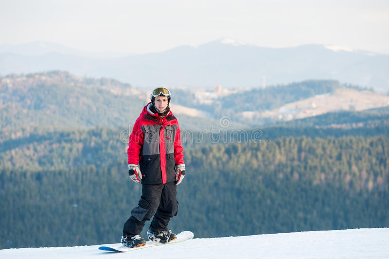 Male boarder on his snowboard at winer resort. Cool snowboarder wearing helmet, red jacket, gloves and pants standing on top of a mountain and looking at the stock photo