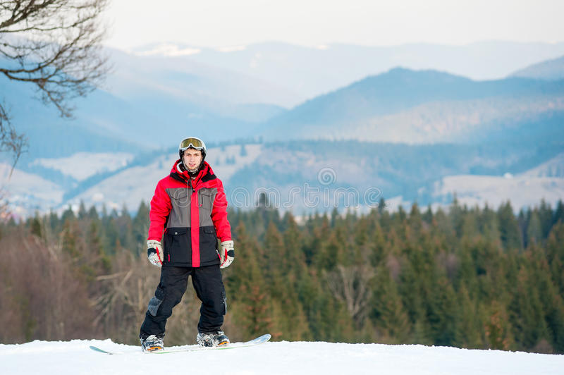 Male boarder on his snowboard at winer resort. Portrait of snowboarder wearing helmet, red jacket, gloves and pants standing on top of a mountain and looking at stock image