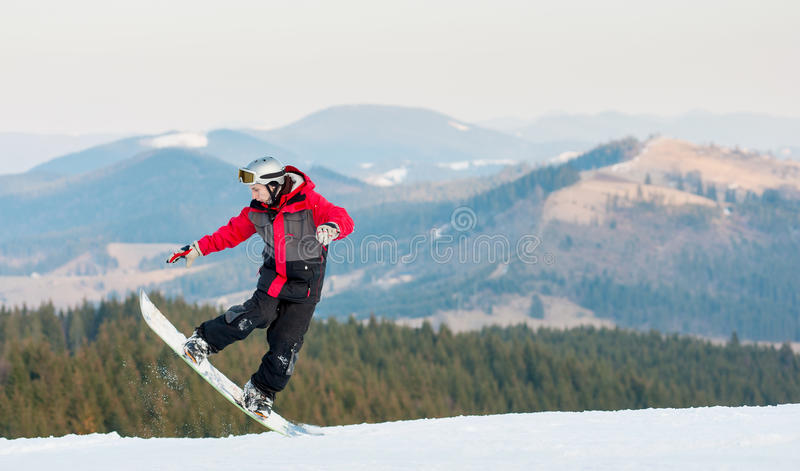 Male boarder on his snowboard at winer resort. Snowboarder man in action into snow powder at the mountains on background forest, hills and the sky. Extreme stock image