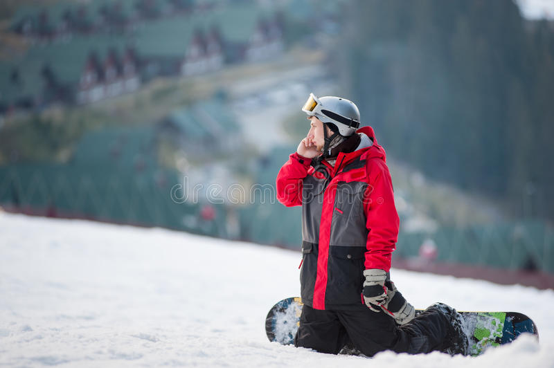 Male boarder on his snowboard at winer resort. Snowboarder resting on ski slope, he& x27;s kneeling, looking away and talking on the phone, winter sports concept royalty free stock images